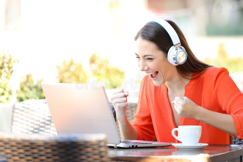 H?llande ?gonen p? och lyssnande massmedia f?r upphetsad kvinna p? b?rbara datorn royaltyfri bild