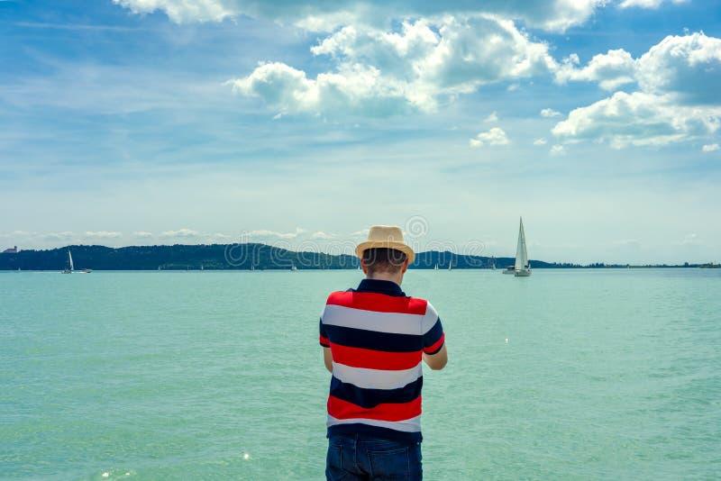 Hållande ögonen på segelbåtar för man från kusten på Balaton sjöUngern royaltyfri foto