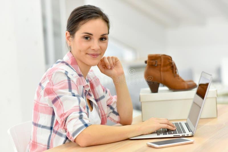 Hållande ögonen på skoförsäljningar för ung kvinna på internet arkivfoto