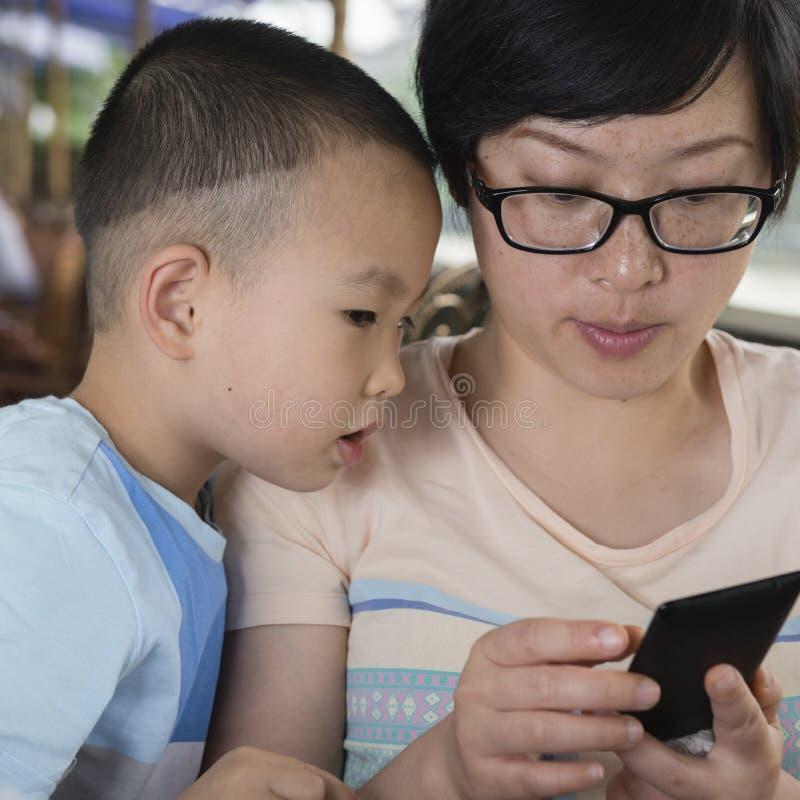 Hållande ögonen på smartphone för pojke royaltyfri foto
