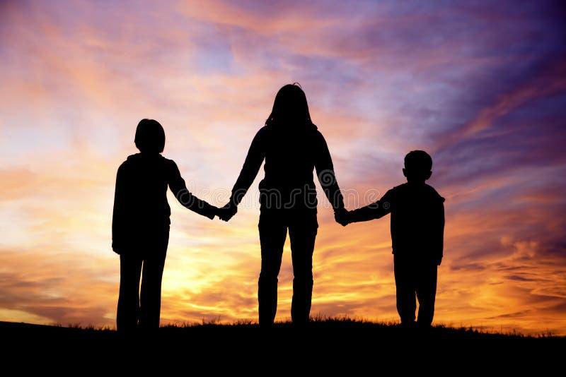 Hållande ögonen på solnedgång för familj. royaltyfri foto