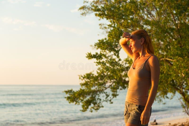 Hållande ögonen på solnedgång för kvinna royaltyfria foton