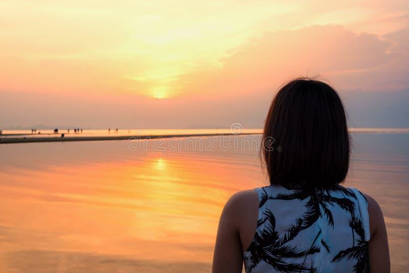 Hållande ögonen på solnedgång för kvinna på stranden arkivfoton