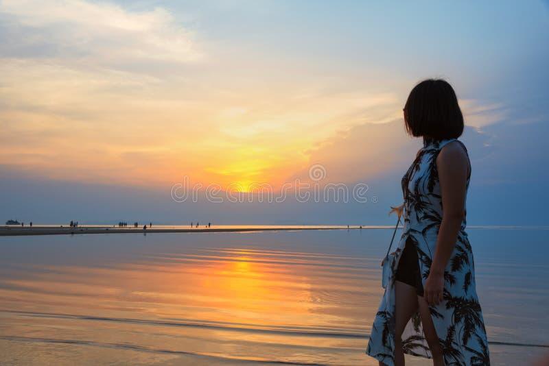 Hållande ögonen på solnedgång för kvinna på stranden royaltyfria bilder