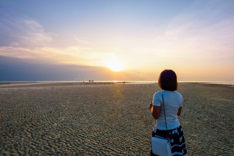 Hållande ögonen på solnedgång för kvinna på stranden arkivbild