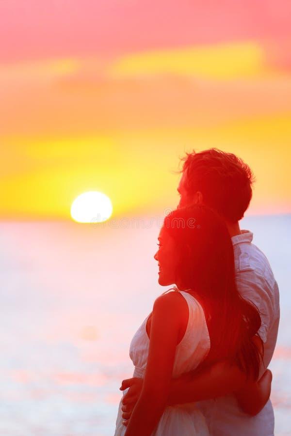Hållande ögonen på solnedgång för lyckliga par på strandsemestern arkivfoton