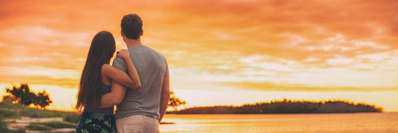 Hållande ögonen på solnedgång för par på sommaraffärsföretaglopp på det panorama- banret för strand - glödhimmelbakgrund på arkivbilder