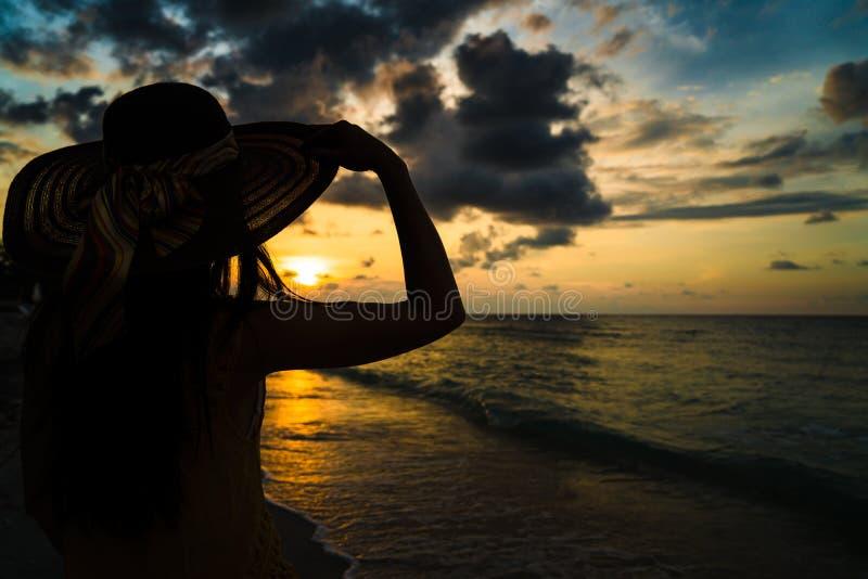 Hållande ögonen på solnedgång för turist- kvinna på havstranden royaltyfria foton