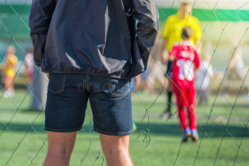 Hållande ögonen på son för fader som spelar fotbollleken royaltyfri bild