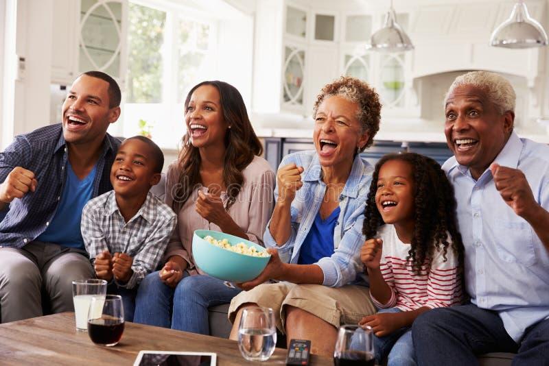 Hållande ögonen på sport för mång- utvecklingssvartfamilj på TV hemma arkivbilder