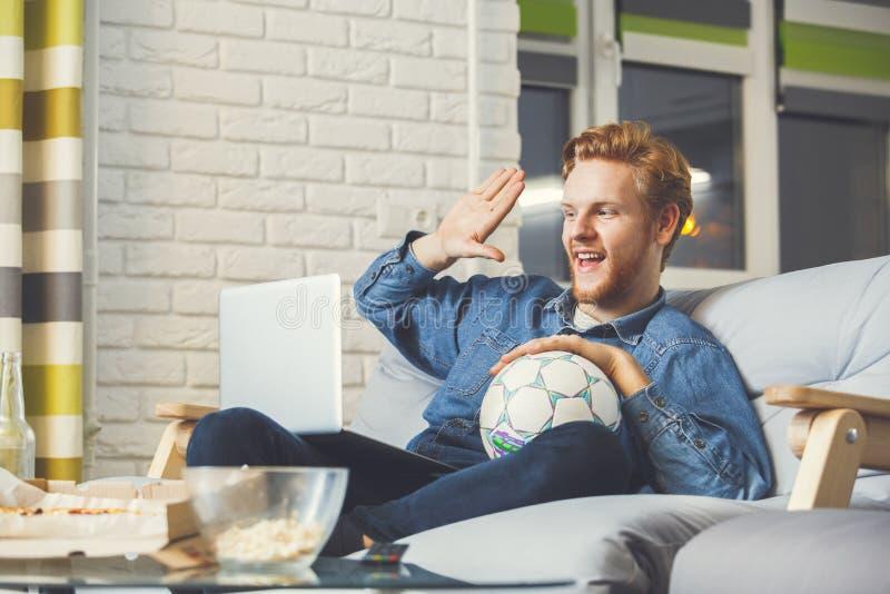 Hållande ögonen på sport för man på hemmastadd ensam video appell för tv royaltyfri foto