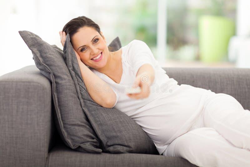 Hållande ögonen på television för gravid kvinna royaltyfri bild