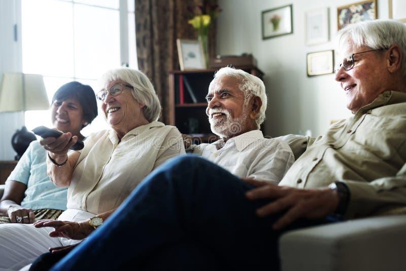 Hållande ögonen på television för högt folk tillsammans arkivbild