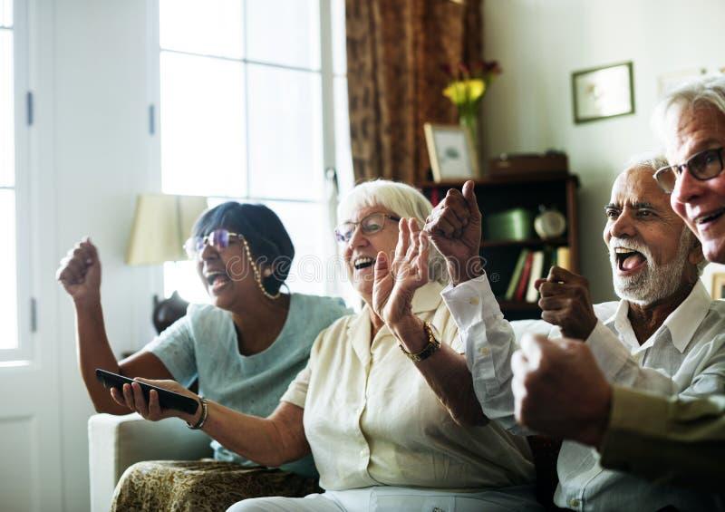 Hållande ögonen på television för högt folk tillsammans royaltyfri fotografi