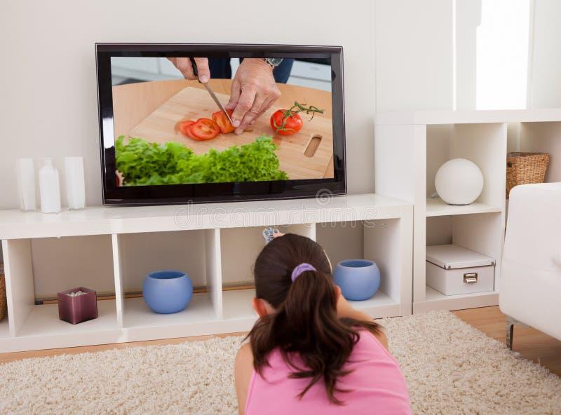 Hållande ögonen på television för kvinna royaltyfri foto