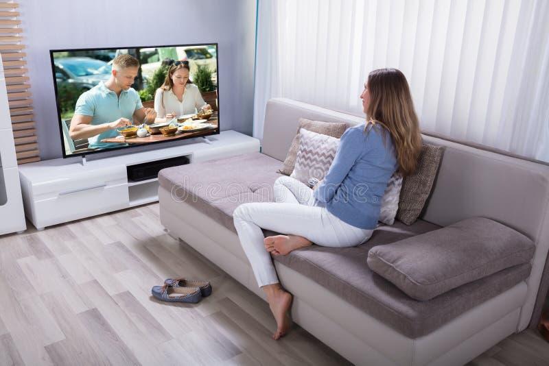Hållande ögonen på television för kvinna hemma arkivfoto