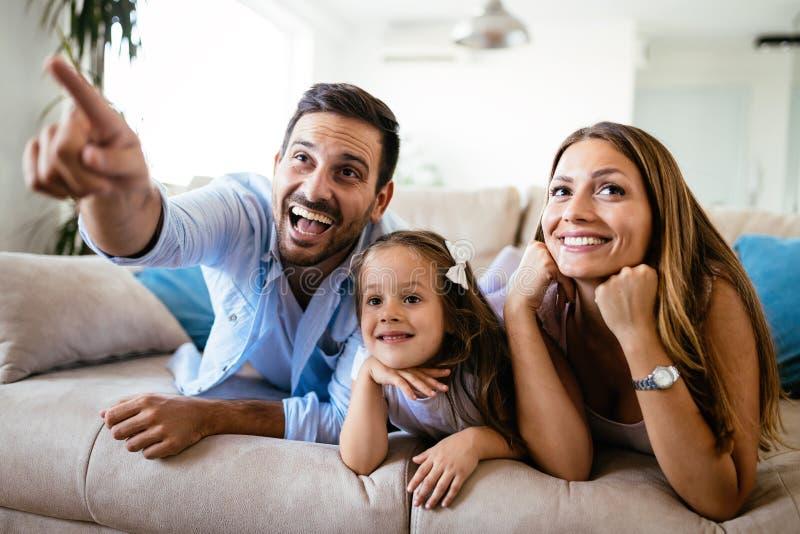 Hållande ögonen på television för lycklig familj på deras hem royaltyfria bilder