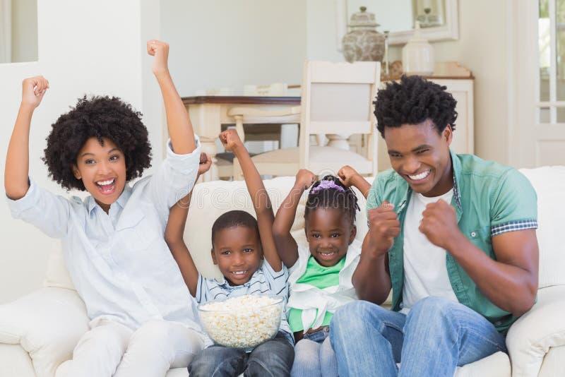 Hållande ögonen på television för lycklig familj som äter popcorn arkivbilder