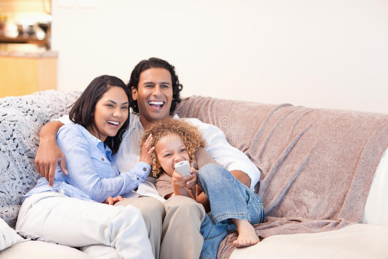 Hållande ögonen på television för lycklig familj tillsammans royaltyfria foton