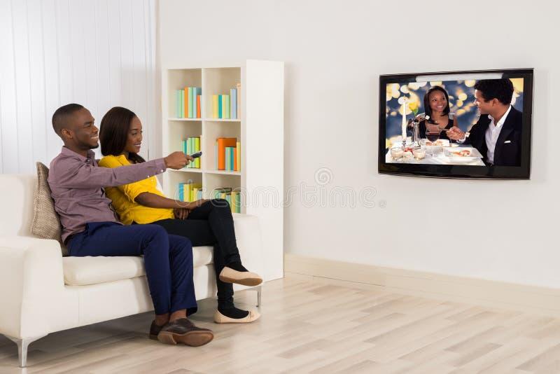 Hållande ögonen på television för lyckliga par royaltyfri fotografi