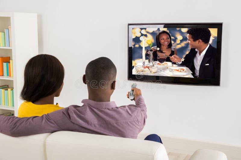 Hållande ögonen på television för lyckliga par royaltyfri foto