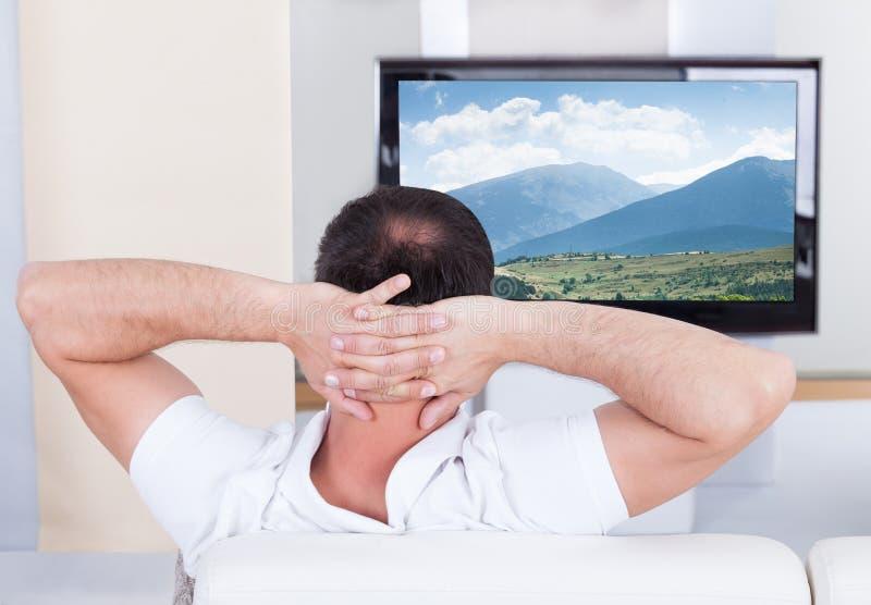 Hållande ögonen på television för man hemma royaltyfri fotografi