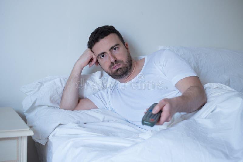 Hållande ögonen på television för man som ligger i säng fotografering för bildbyråer