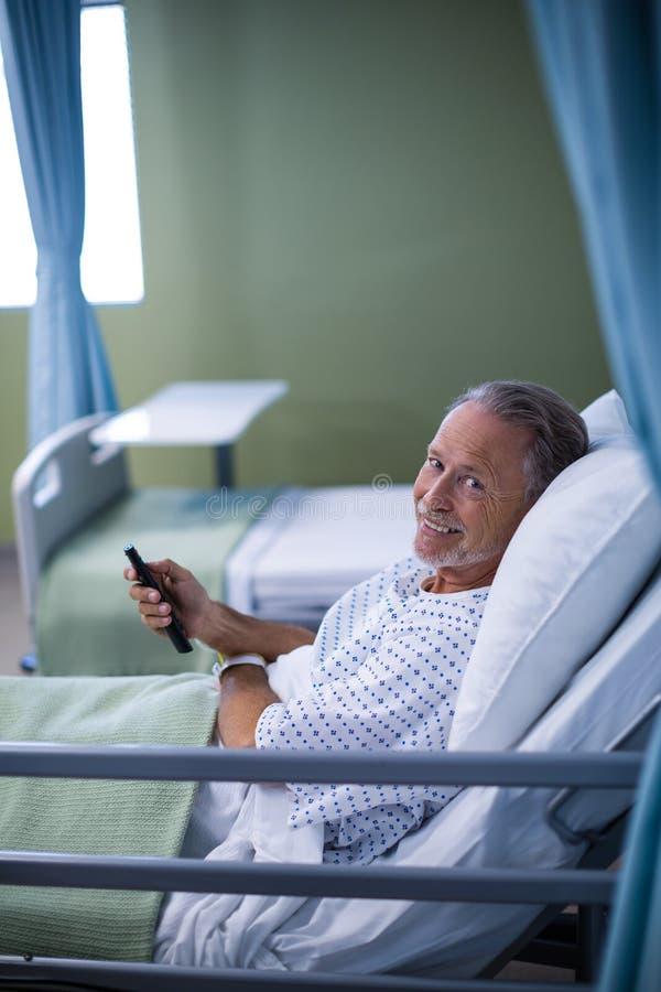 Hållande ögonen på television för patient på sängen royaltyfria foton