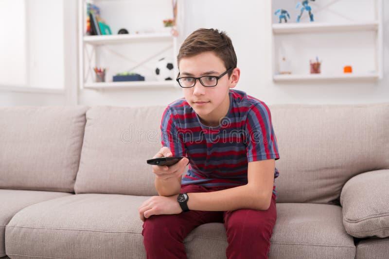 Hållande ögonen på television för tonåringpojke, genom att använda fjärrkontroll fotografering för bildbyråer
