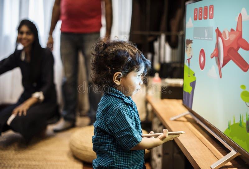 Hållande ögonen på television för ung indisk pojke royaltyfri foto