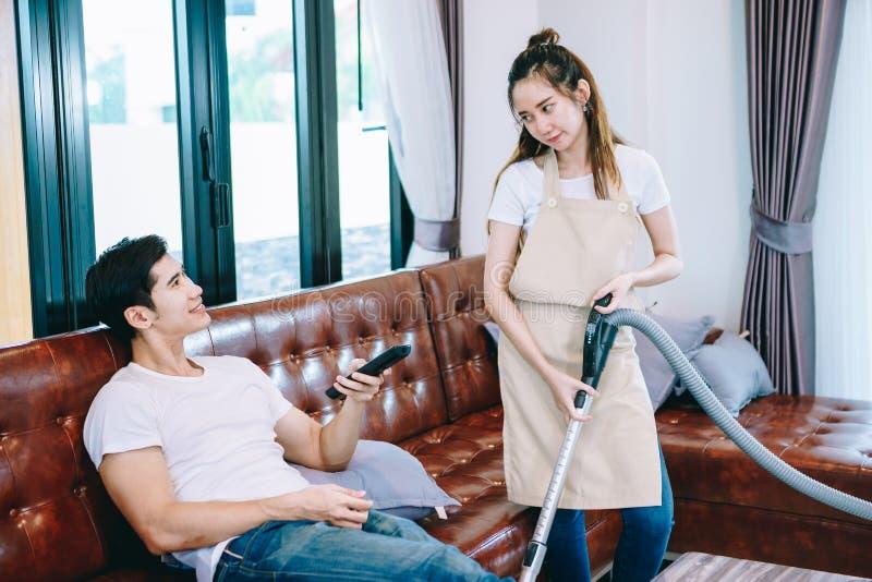 Hållande ögonen på TV för asiatiska tonåriga par tillsammans lyckligt fotografering för bildbyråer