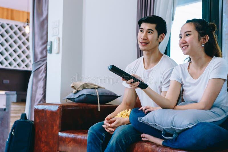 Hållande ögonen på TV för asiatiska tonåriga par tillsammans lyckligt arkivbild