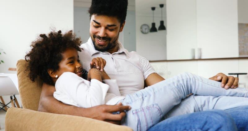 Hållande ögonen på tv för avkopplad afrikansk amerikanfamilj fotografering för bildbyråer