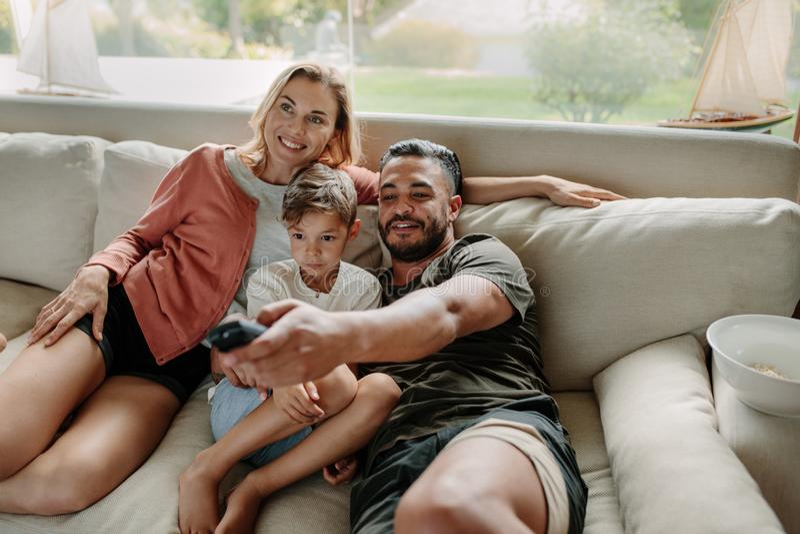 Hållande ögonen på tv för avkopplad familj tillsammans arkivfoto