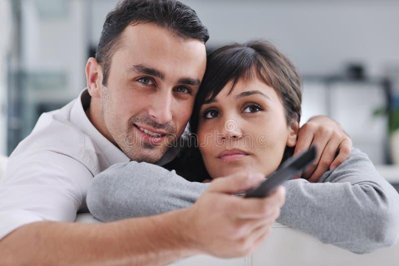 Hållande ögonen på tv för avkopplade unga par hemma royaltyfria foton