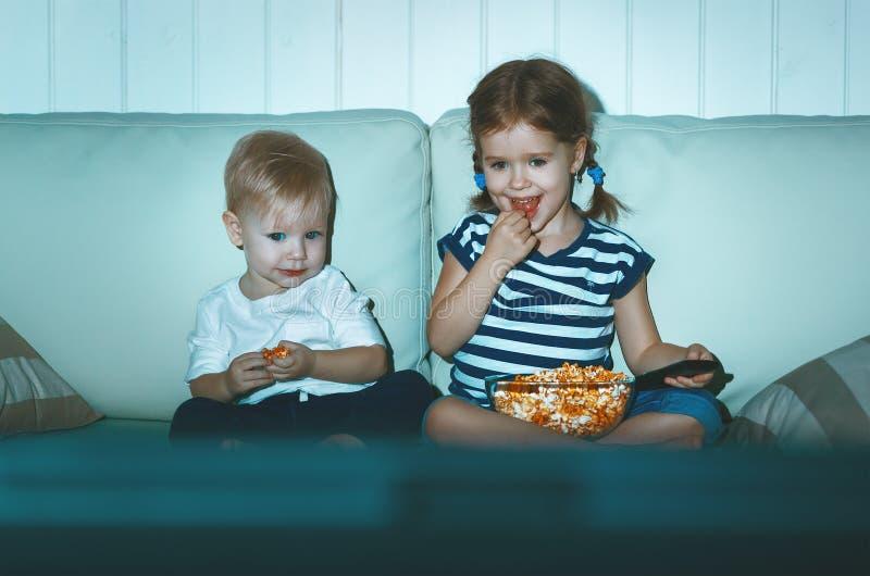 Hållande ögonen på TV för barnsyskongrupp i afton fotografering för bildbyråer