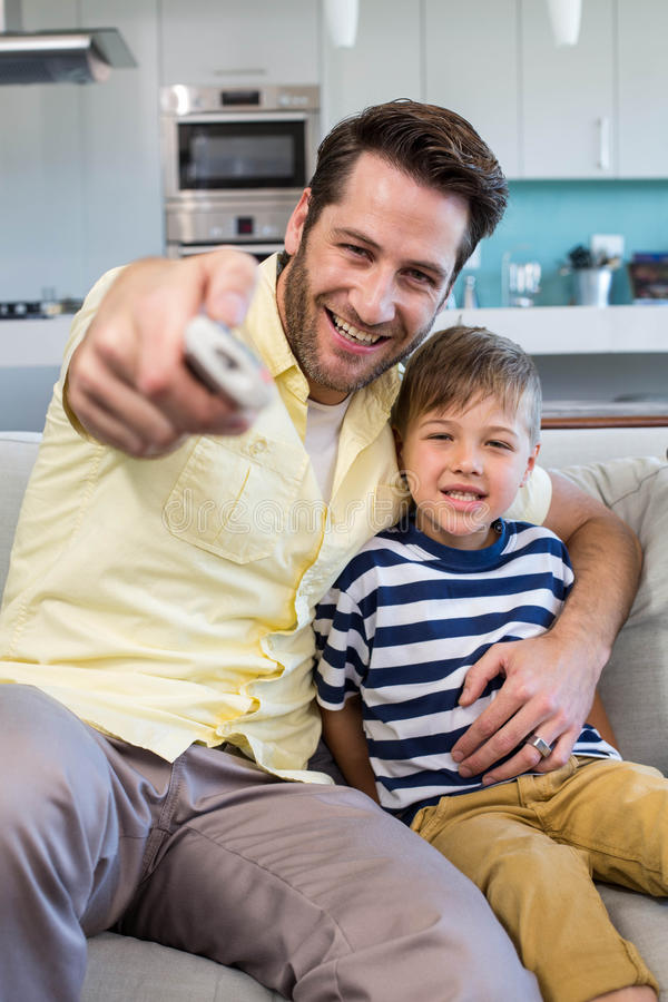 Hållande ögonen på tv för fader och för son tillsammans på soffan arkivfoto