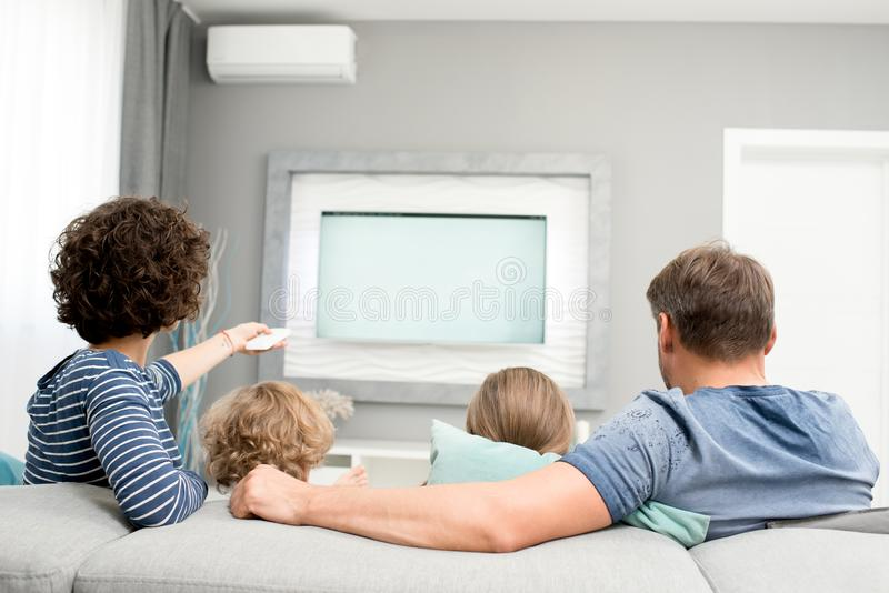 Hållande ögonen på TV för familj, baksidasikt fotografering för bildbyråer