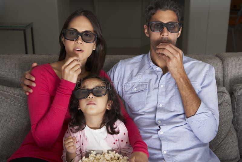 Hållande ögonen på TV för familj som bär exponeringsglas 3D och äter popcorn arkivbild