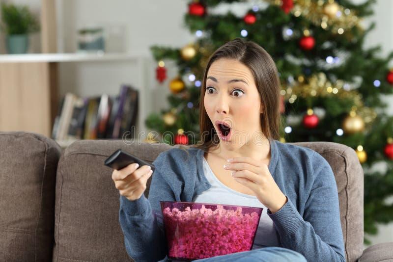 Hållande ögonen på tv för häpen kvinna i julferier royaltyfri foto