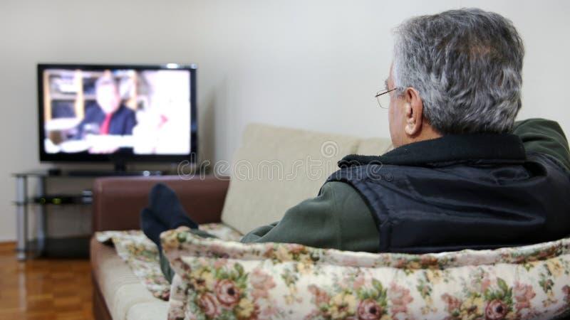 Hållande ögonen på TV för hög man royaltyfri foto