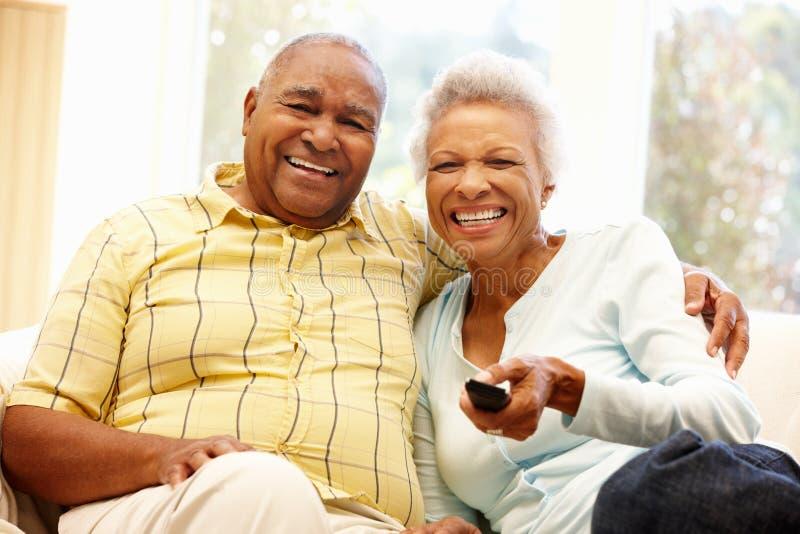 Hållande ögonen på TV för höga afrikansk amerikanpar royaltyfri foto