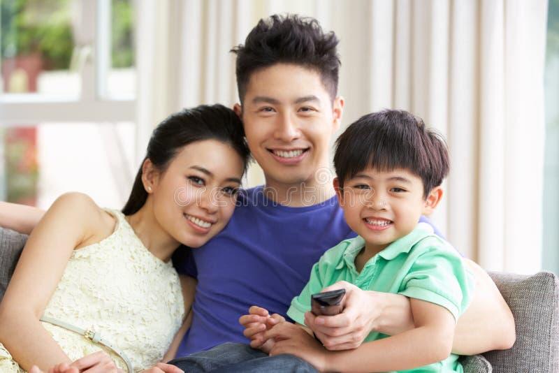 Hållande ögonen på TV för kinesisk familj på sofaen tillsammans royaltyfri fotografi