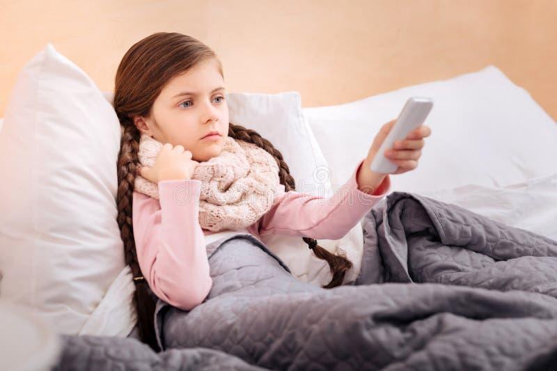 Hållande ögonen på TV för liten flicka, medan vila i hennes säng arkivfoton