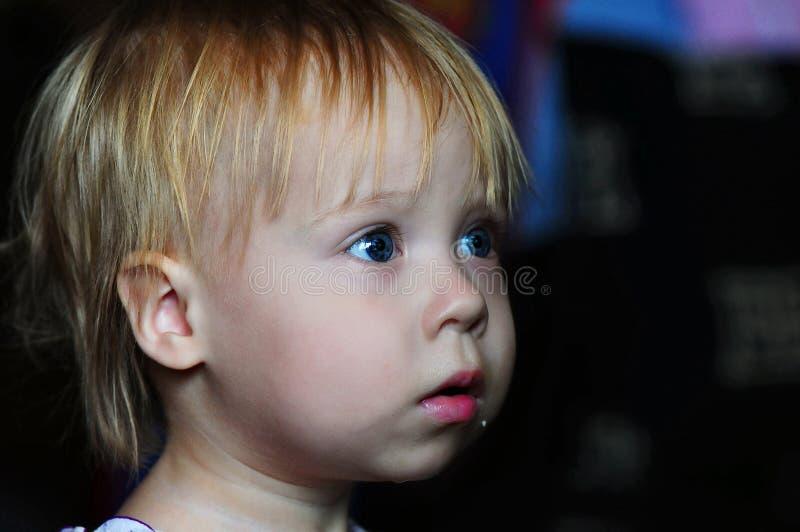 Hållande ögonen på TV för liten härlig flicka hemma arkivfoto