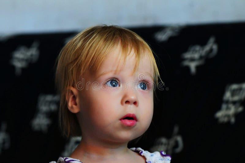 Hållande ögonen på TV för liten härlig flicka hemma royaltyfri bild