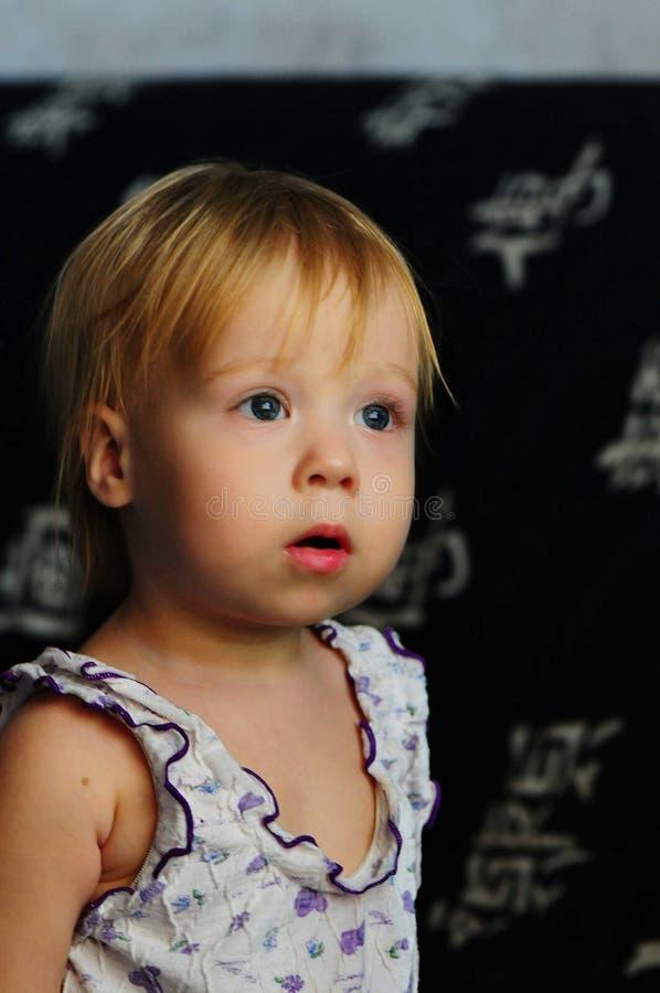 Hållande ögonen på TV för liten härlig flicka hemma fotografering för bildbyråer