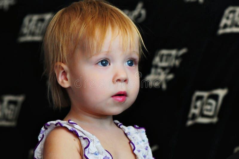 Hållande ögonen på TV för liten härlig flicka hemma arkivbild