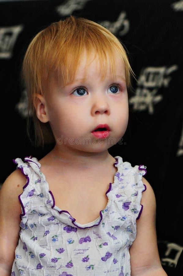 Hållande ögonen på TV för liten härlig flicka hemma royaltyfri foto