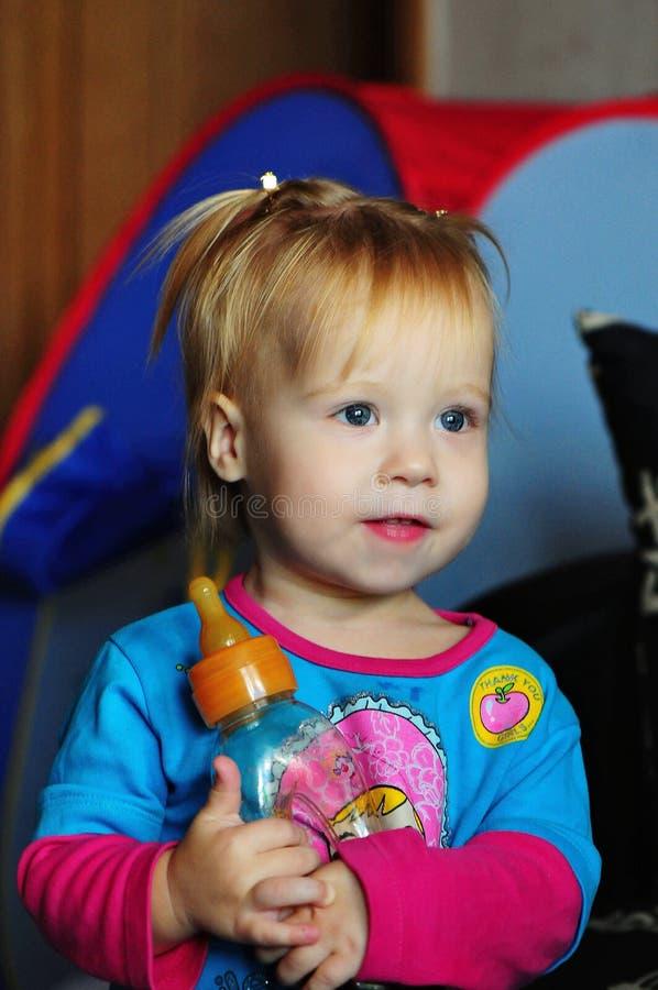 Hållande ögonen på TV för liten härlig flicka hemma arkivfoton